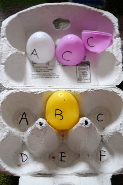 Playing with alphabet letters written on plastic eggs - fun activity for kids to teach them the letters