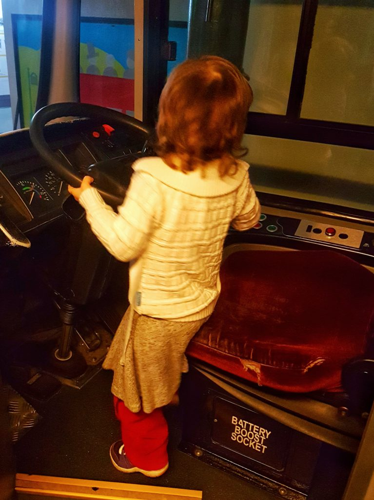 Children driving a double decker bus at London Transport Museum