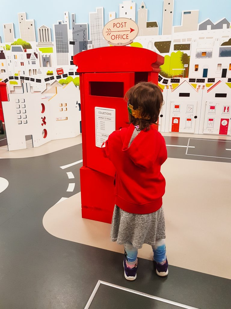 Child playing-pretend, being a 'postie' for the day in London at Postal Museum